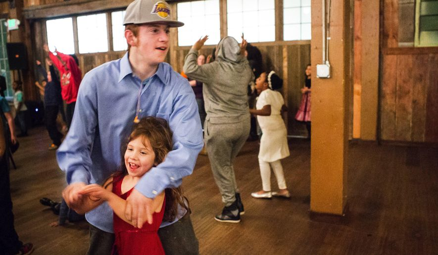 ADVANCE FOR THE WEEKEND OF JAN. 23 - In this Saturday, Jan. 16, 2016 photo, big brother Tyrus Gilbertson whisks around sister Corrine, 6, as they dance to tunes from the Michael Benson Band during a special event donated to people staying at Mary's Place shelter at Sodo Park in Seattle. (Lindsey Wasson/The Seattle Times via AP) MANDATORY CREDIT