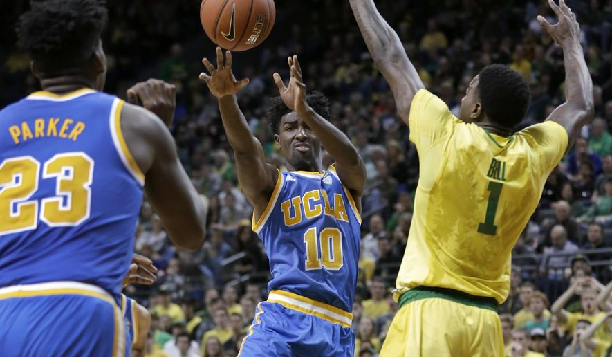 UCLA's Wonder Smith, center, passes the ball to UCLA's Tony Parker, left, while being defended by Oregon's Jordan Bell, right, during the second half of an NCAA college basketball game Saturday, Jan. 23, 2016, in Eugene, Ore. (AP Photo/Ryan Kang)