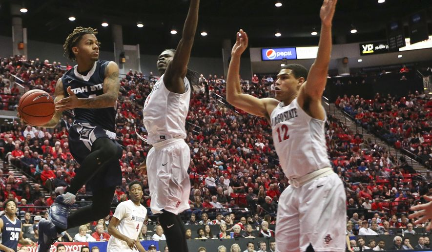 Utah State guard Shane Rector looks for a place to pass the ball as he drives the baseline against San Diego State forward Angelo Chol, and Trey Kell, right, in the first half of an NCAA college basketball game Saturday, Jan. 23, 2016, in San Diego. (AP Photo/Lenny Ignelzi)