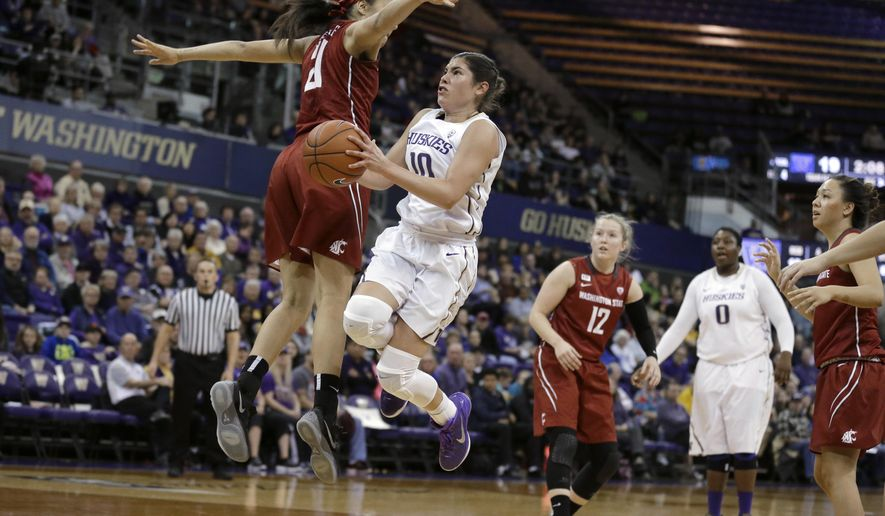 Washington guard Kelsey Plum, second from left, jumps to put up a shot around Washington State forward Nike McClure, left, during the first half of an NCAA college basketball game, Saturday, Jan. 23, 2016, in Seattle. (AP Photo/Ted S. Warren)