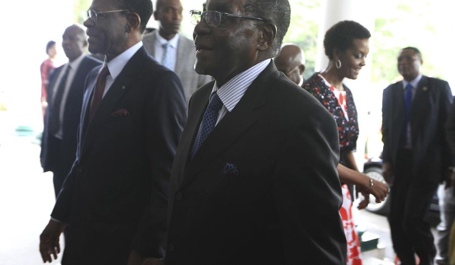 Zimbabwean President Robert Mugabe, right, holds hands with Equatorial Guinea President Teodoro  Obiang Nguema Mbasago at State House in Harare, Saturday,  January, 23, 2016. Mugabe,91, who was  rumored to be sick and hospitalized returned from his annual vacation Friday. (AP Photo/Tsvangirayi Mukwazhi)