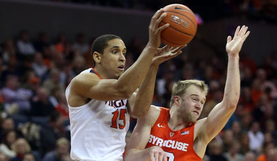Virginia guard Malcolm Brogdon (15) passes the ball next to Syracuse guard Trevor Cooney (10) during an Atlantic Coast Conference basketball game, Sunday Jan. 24, 2016, in Charlottesville, Va. Virginia  defeated Syracuse 73-65. (AP Photo/Andrew Shurtleff)
