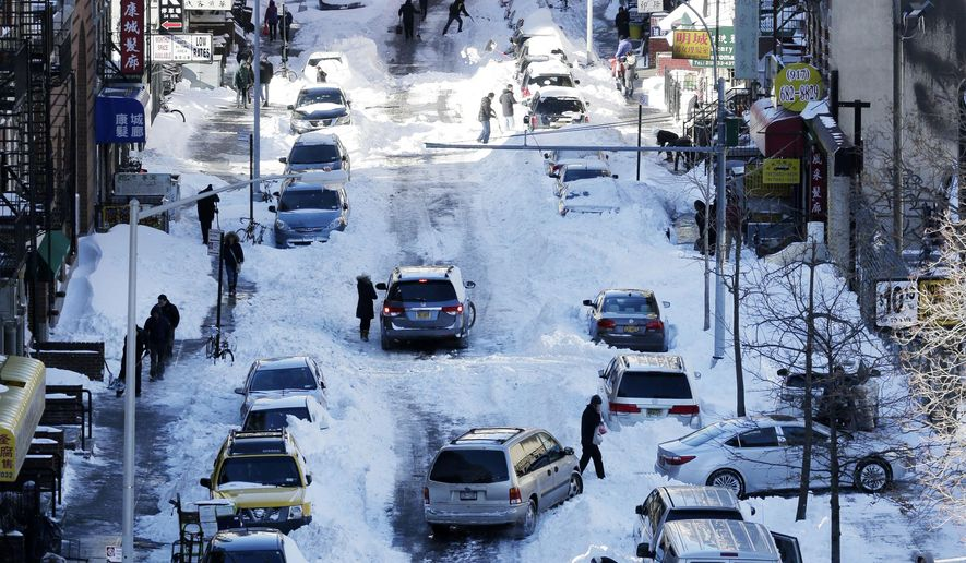 People clear snow from parked cars on Henry Street in the Chinatown neighborhood in New York on Sunday, Jan. 24, 2016. Millions of Americans began digging out Sunday from a mammoth blizzard that set a new single-day snowfall record in Washington and New York City. (AP Photo/Peter Morgan)