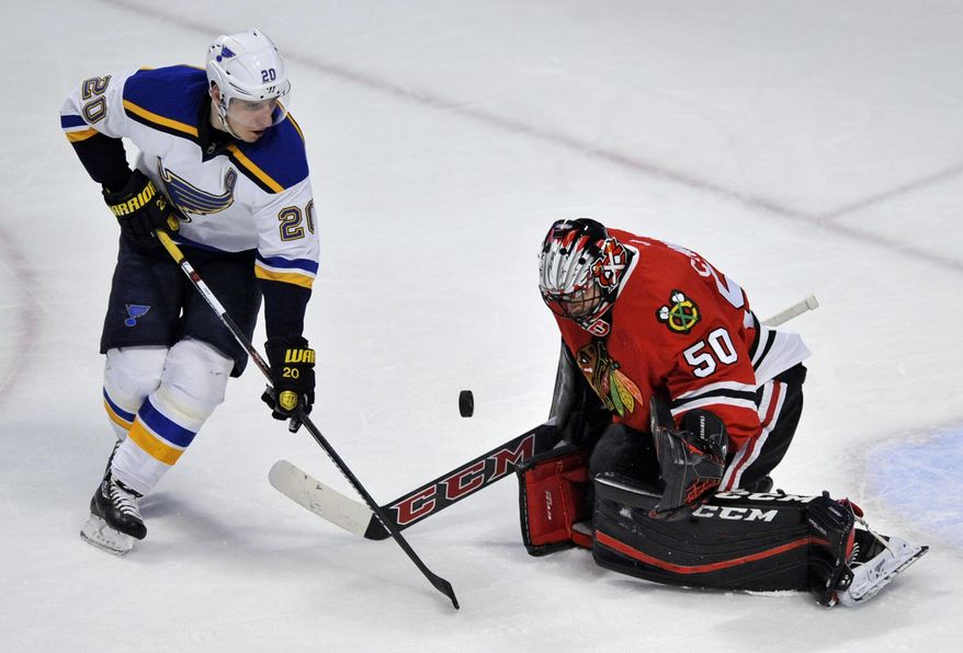 Chicago Blackhawks goalie Corey Crawford (50), makes a save against St. Louis Blues' Alexander Steen (20), during the first period of a hockey game Sunday, Jan. 24, 2016, in Chicago. (AP Photo/Paul Beaty)