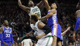 Boston Celtics' Marcus Smart, top left, puts up the shot as he is fouled by Philadelphia 76ers' Jahlil Okafor, top right, as Boston Celtics' Jared Sullinger, bottom tries to get out of the way during the first half of an NBA basketball game, Sunday, Jan. 24, 2016, in Philadelphia. (AP Photo/Chris Szagola)