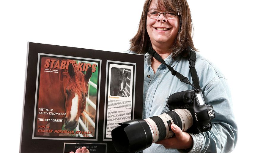 ADVANCE FOR USE SUNDAY, JAN. 24 - In this photo taken Jan. 12, 2016, photographer Faye Zmek, of Chapman, holds a photograph she took of her daughter Shayla's horse, which was used as the cover photo for Stable Kids magazine, as she poses for a photo in Grand Island, Neb. After her daughter was killed in a car accident in 1994, Zmek combined her love of horses and photography to help her move on from the tragedy, and has gone on to create a thriving business in the horse photography world. (Barrett Stinson/The Independent via AP) MANDATORY CREDIT, TV OUT, RADIO OUT, MAGS OUT.