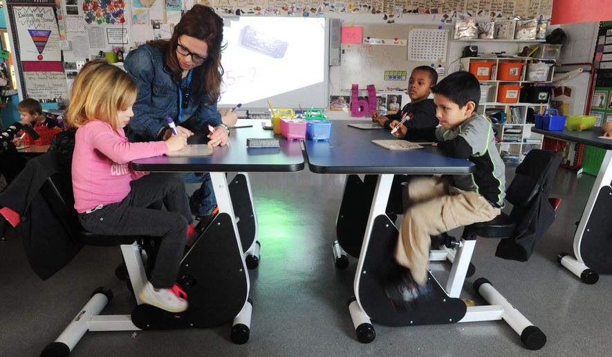 In this photo taken on Tuesday, Jan. 19, 2016, Estes Elementary School kindergarten students Evelyn Bolmer, 5, front left, Jase Bellamy, 6, back right, and Eric Guarneros, 6, front right, listen as their teacher Faith Harralson assists Bolmer with a math equation as they ride pedal desks in Owensboro, Ky. Harralson won a $12,000 grant from the school system to install the desks in her classroom. (Jenny Sevcik /The Messenger-Inquirer via AP) MANDATORY CREDIT
