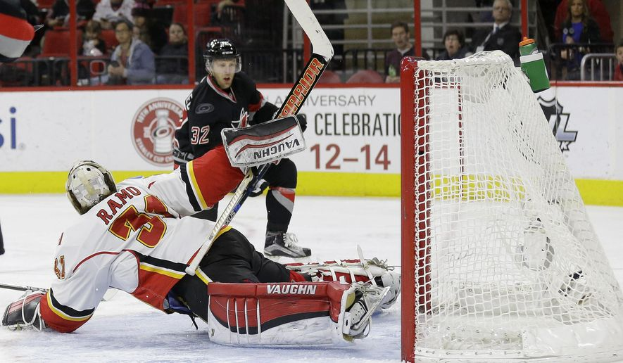 Carolina Hurricanes' Kris Versteeg (32) scores against Calgary Flames goalie Karri Ramo (31), of Finland, during the second period of an NHL hockey game in Raleigh, N.C., Sunday, Jan. 24, 2016. (AP Photo/Gerry Broome)