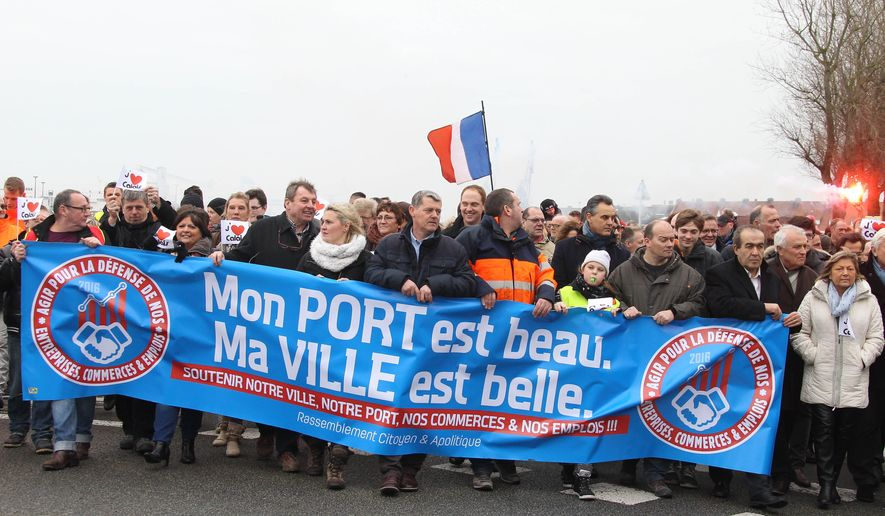 "Shop owners and local business people hold a banner reading ""My port is beautiful, My city is beautiful"" during a demonstration in Calais to call attention to the impact that Europe's migrant crisis is having on their town's local economy, in Calais, northern France, Sunday, Jan. 24, 2016. Calais has become a flashpoint in Europe's migrant crisis as thousands of migrants seeking to cross into Britain camp out in squalid conditions and periodically wreak havoc on service at the port and nearby rail facilities. (Photo/Michel Spingler)"