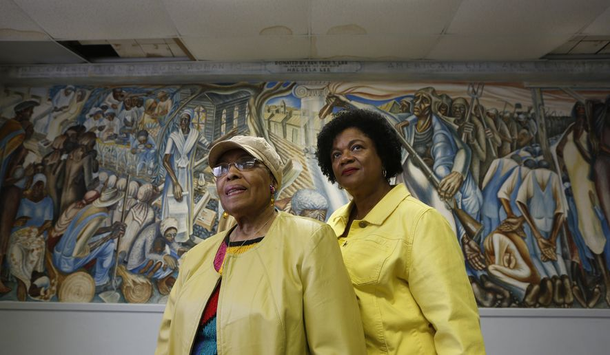 Charlotte Kelly Bryant, president of the Blue Triangle Multi-Cultural Association and Lucy Bremond with the Blue Triangle Multi-Cultural Association pose for a photo Wednesday, Jan. 20, 2016, in Houston. The group bought the building, which has a large John Biggers mural depicting the strength of black women that is endangered because of a leaking roof in one of the rooms. Repairs estimated at $250,000 are required to prevent irreparable damage to the priceless artwork. (Steve Gonzales/Houston Chronicle via AP)
