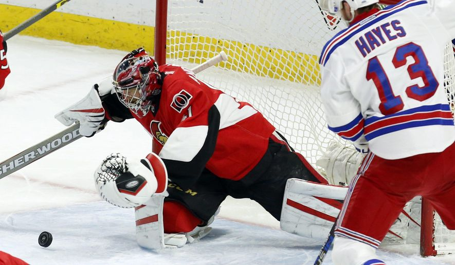 Ottawa Senators goaltender Craig Anderson (41) dives for the puck as New York Rangers Kevin Hayes (13) looks on during during first period NHL hockey action in Ottawa, Ontario, on Sunday, Jan. 24, 2016. (Fred Chartrand/The Canadian Press via AP) MANDATORY CREDIT