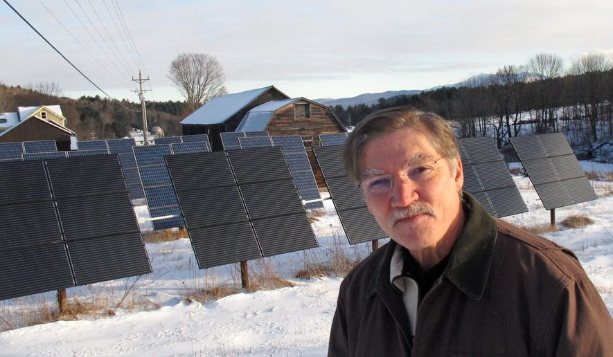 In this photo taken on Friday, Jan. 22, 2016, Jeff Forward stands in front of solar panels, which are part of a community array, on his property in Richmond, Vt.  Vermont's commitment to renewable energy has created a job-producing boom in renewable energy projects that have seen tens of thousands of solar panels pop-up across the state.  Now due to the success in harnessing the alternative energy, many are trying to cope with how to regulate the amount of power small producers can send to the electrical grid. (AP Photo/Wilson Ring)
