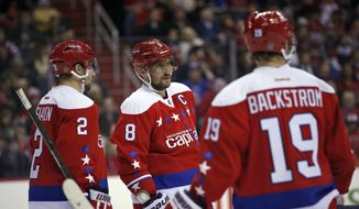 Washington Capitals defenseman Matt Niskanen (2), left wing Alex Ovechkin (8), from Russia, and center Nicklas Backstrom (19), from Sweden, stand during a break in the second period of an NHL hockey game against the New York Rangers, Sunday, Jan. 17, 2016, in Washington. (AP Photo/Alex Brandon)