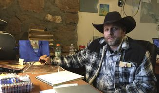 Ammon Bundy sits at a desk he was using at the Malheur National Wildlife Refuge in Oregon on Friday, Jan. 22, 2016.  (AP Photo/Keith Ridler) ** FILE **