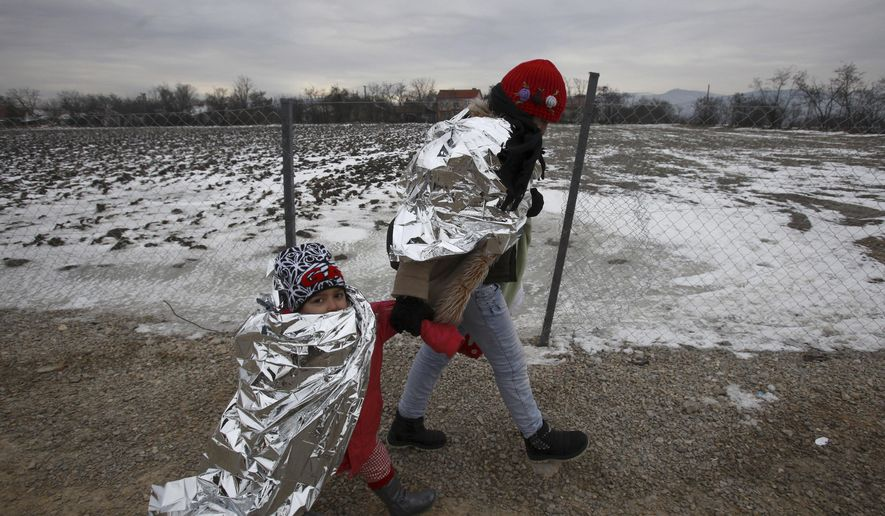 Refugee woman and a child, wrapped in thermal blankets, walk in freezing weather towards the border with Serbia from the transit center for refugees near northern Macedonian village of Tabanovce on their journey toward Western Europe Sunday, Jan. 24, 2016. Macedonia, Serbia and Croatia, the countries on the so-called Balkan migrant corridor that starts in Greece, are only letting in people whose stated final destination is Germany or Austria. (AP Photo/Boris Grdanoski)