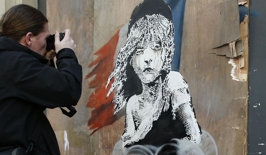 A man takes a photo of a new artwork by British artist Banksy opposite the French Embassy, in London, Monday, Jan. 25, 2016. The artwork depicts the young girl from the musical Les Miserables with tears streaming from her eyes as a can of CS gas lies beneath her. The work is criticising the use of teargas in the refugee camp in Calais. (AP Photo/Alastair Grant)