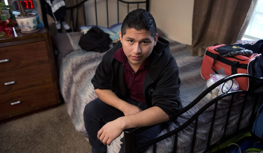 Marvin Velasco, 15, poses at his new home in Los Angeles on Monday, Jan. 11, 2016. In September 2014, Velasco said he soon realized that nine other people lived in the apartment of his first sponsor in the United States, a distant relative whom he had never met. The sponsor told Velasco he would be punished if he left the apartment, and demanded rent payments. When Velasco told the sponsor he wanted to study, the man called the boy's parents in Guatemala, threatening to kick him out if they didn't pay. Then he started withholding food, Velasco said. (AP Photo/Mark J. Terrill)