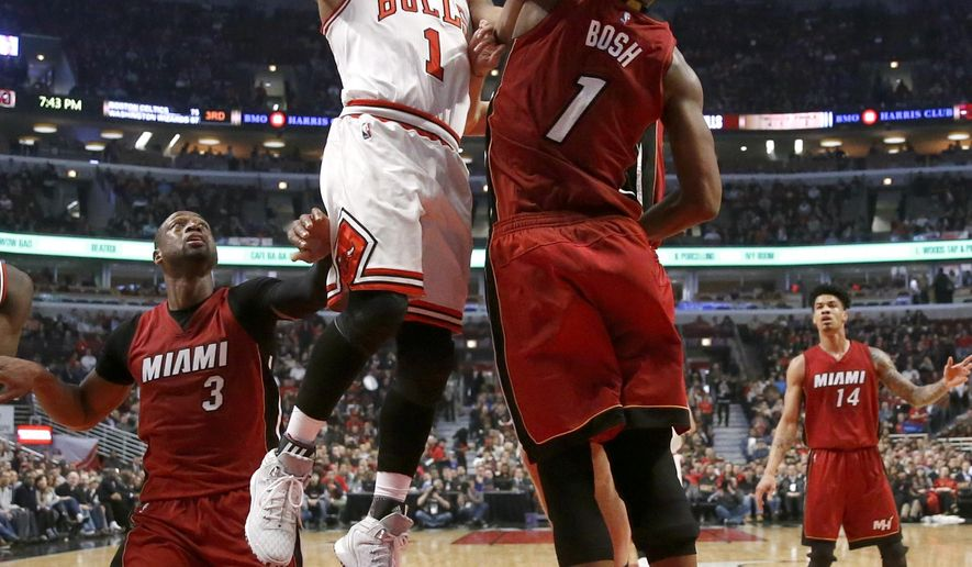 Chicago Bulls guard Derrick Rose (1) shoots over Miami Heat forward Chris Bosh (1) as Dwyane Wade (3) watches during the first half of an NBA basketball game, Monday, Jan. 25, 2016, in Chicago. (AP Photo/Charles Rex Arbogast)