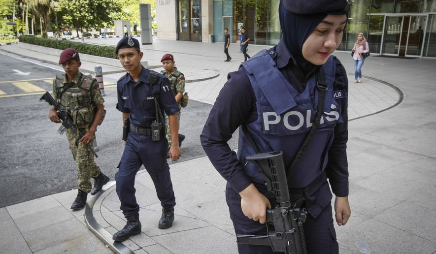 Malaysian military and police personnel patrol an outside shopping mall in Kuala Lumpur, Malaysia, Monday, Jan. 25, 2016. Malaysia's leader has defended strict security laws to fight terrorism as the Islamic State group warned of revenge over a crackdown on its members. (AP Photo/Joshua Paul)