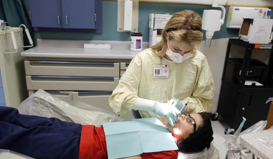In this Friday, Jan. 22, 2016 photo, dental resident Madison Myers Galloway checks the teeth of Justin Perez, 11, during an office visit at Riley Hospital for Children's Department of Pediatric Dentistry in Indianapolis. A federal report says three out of four children did not receive all required dental services, such as regular checkups and fluoride treatments, in Medicaid programs in four states. One in four kids failed to see a dentist at all. (AP Photo/Michael Conroy)