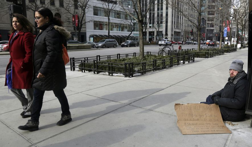 A man, right, panhandles on the street Monday, Jan. 25, 2016, in Chicago. A lawsuit brought by panhandlers who say they lose up to $10 a day because authorities bar them from a popular public square in Chicago is set to go to trial. The trial that starts Monday in Chicago federal court is a rare instance of jurors being asked to decide the issue of panhandlers' rights. (AP Photo/M. Spencer Green)
