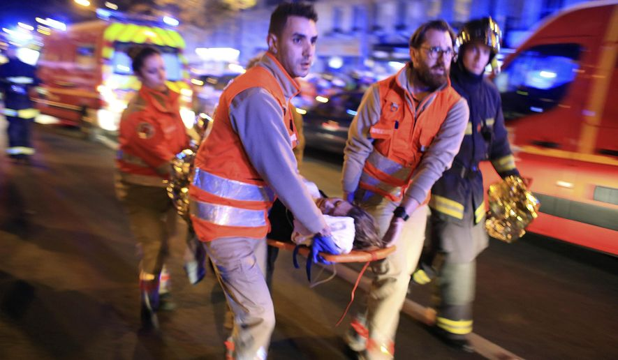 FILE - In this Nov. 13, 2015, file photo, a woman is evacuated from the Bataclan concert hall after gunmen attacked the venue in Paris. New video released Sunday, Jan. 24, 2016, by the Islamic State group shows the extremists who carried out the Nov. 13 attacks in Paris committing atrocities in IS-controlled territory while plotting the slaughter in the French capital. The video shows the extent of the planning that went into the operation, which French authorities have said from the beginning was planned in Syria. (AP Photo/Thibault Camus, File)