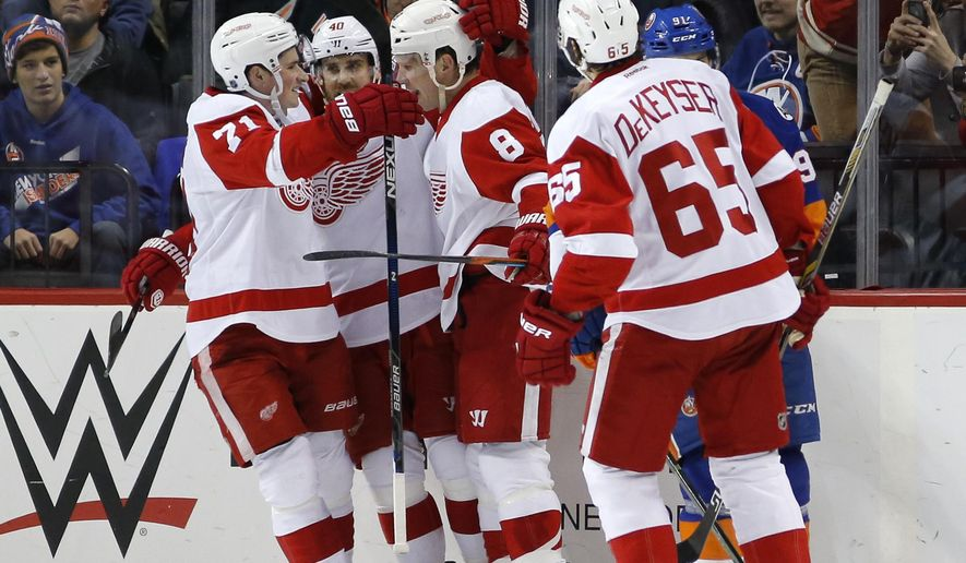 Detroit Red Wings center Dylan Larkin (71) and Red Wings left wing Henrik Zetterberg (40) of Sweden celebrate with Red Wings left wing Justin Abdelkader (8) after Abdelkader scored a goal as Red Wings defenseman Danny DeKeyser (65) looks on in the second period of an NHL hockey game in New York, Monday, Jan. 25, 2016. (AP Photo/Kathy Willens)