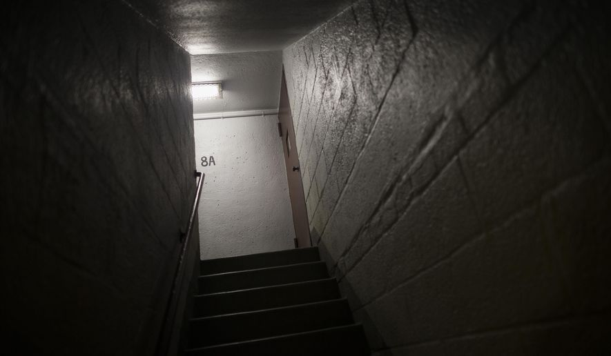 In this Nov. 22, 2014, file photo, a light illuminates the stairwell where Akai Gurley was fatally shot by rookie NYPD officer Peter Liang at the Louis Pink Houses public housing complex in the Brooklyn borough of New York. (AP Photo/John Minchillo, File)