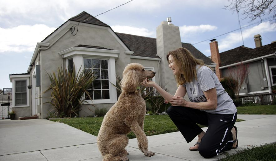 In this Friday, Jan. 15, 2016, photo, Therese Lehane poses for a photo with her dog Rudy outside her house in San Jose, Calif. Lehane is renting out two of her rooms to Super Bowl news crews. In the San Francisco Bay Area, where high rents are legend, residents looking to make a quick buck are offering their homes at super-sized prices to the 1 million visitors expected for the Super Bowl festivities. (AP Photo/Marcio Jose Sanchez)