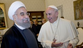 Pope Francis and Iranian President Hassan Rouhani, left, share a laugh during their private audience at the Vatican, Tuesday, Jan. 26, 2016. Iran's president has paid a call on Pope Francis at the Vatican during a European visit aimed at positioning Tehran as a potential top player in efforts to resolve Middle East conflicts, including Syria's civil war. (AP Photo/Andrew Medichini, Pool)