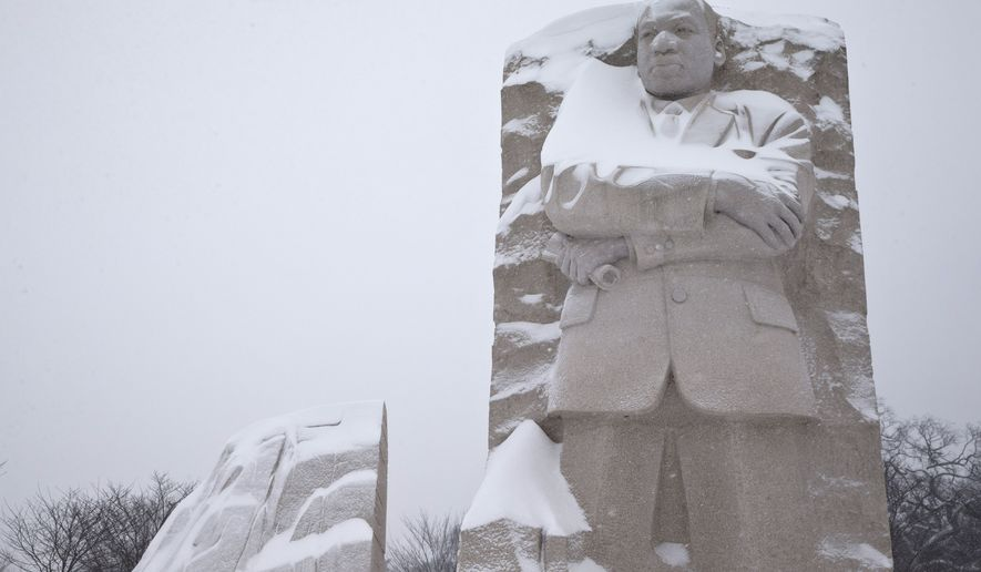 The Martin Luther King, Jr. Memorial is seen with a coating of snow, Saturday, Jan. 23, 2016 in Washington. (AP Photo/Alex Brandon)