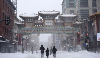 People walk in the snow toward Chinatown's Friendship Archway, Saturday, Jan. 23, 2016, in Washington. A blizzard with hurricane-force winds brought much of the East Coast to a standstill Saturday, dumping as much as 3 feet of snow, stranding tens of thousands of travelers and shutting down the nation's capital and its largest city. (AP Photo/Nick Wass)