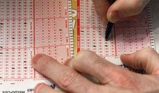 A customer fills out a lottery form for the Mega Millions drawing in Chicago. (Associated Press)
