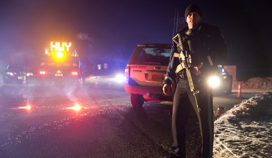 Sgt. Tom Hutchison stands in front of an Oregon State Police roadblock Tuesday on Highway 395 between John Day and Burns. (Associated Press)