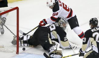 New Jersey Devils' Joseph Blandisi (64) can't get to the puck behind Pittsburgh Penguins goalie Marc-Andre Fleury (29) during the first period of an NHL hockey game in Pittsburgh, Tuesday, Jan. 26, 2016. (AP Photo/Gene J. Puskar)