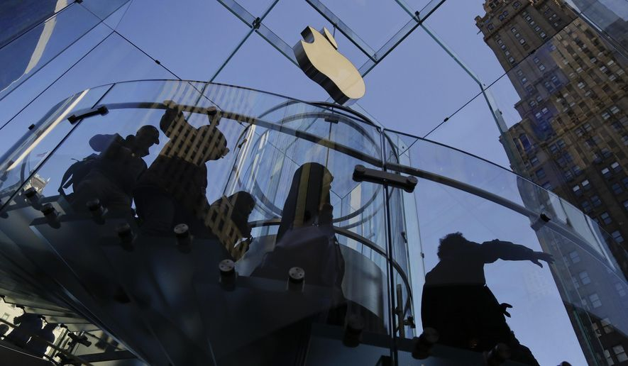 FILE - In this Sept. 19, 2014, file photo, a group of visitors to the Apple store descends a staircase to the showroom below in New York. Apple reports quarterly financial results, Tuesday, Jan. 26, 2016. (AP Photo/Julie Jacobson, File)