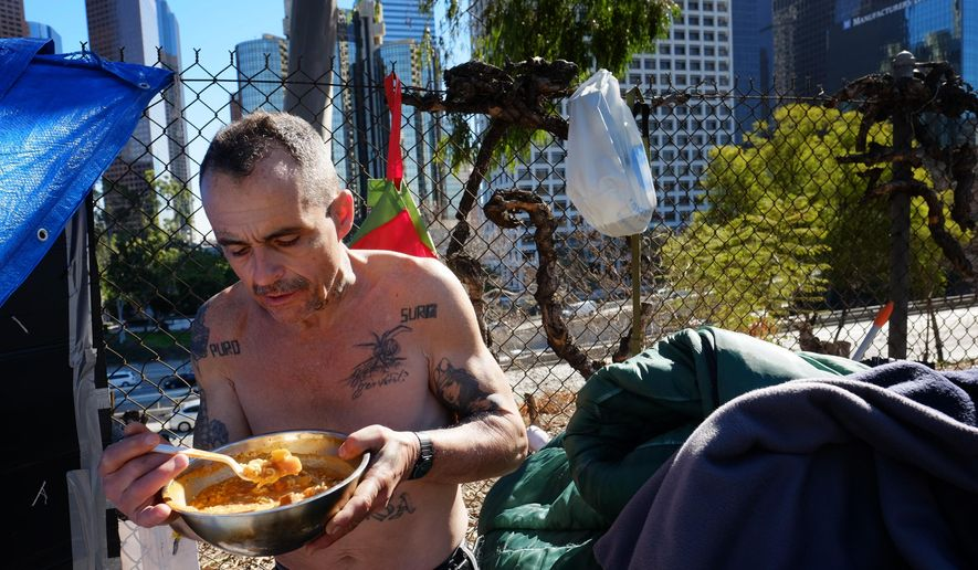 "Eddie, 51, a homeless man who would only give his first name and lives in a tent on the street in downtown Los Angeles, eats his lunch on Tuesday, Jan. 26, 2016. Some 7,000 volunteers will fan out as part of a three-night effort to count homeless people in most of Los Angeles County. Spokeswoman Naomi Goldman said the goal is to ""paint a picture about the state of homelessness."" (AP Photo/Richard Vogel)"