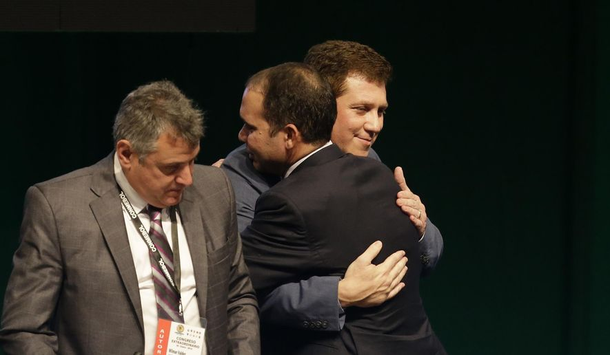 Alejandro Dominguez, of Paraguay, the newly elected president of CONMEBOL, the South American football federation, is embraced by Prince Ali bin al Hussein of Jordan, back to camera, during an extraordinary session of the federation, in Luque, Paraguay, Tuesday, Jan. 26, 2016. Representatives elected Dominguez as their new president, replacing Angel Napout. Standing to the left is the federation's outgoing interim president Wilmar Valdez. (AP Photo/Cesar Olmedo)
