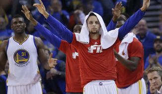 Golden State Warriors' Stephen Curry celebrates from the sideline as teammate Shaun Livingston scores during the first half of an NBA basketball game against the San Antonio Spurs Monday, Jan. 25, 2016, in Oakland, Calif. (AP Photo/Marcio Jose Sanchez)