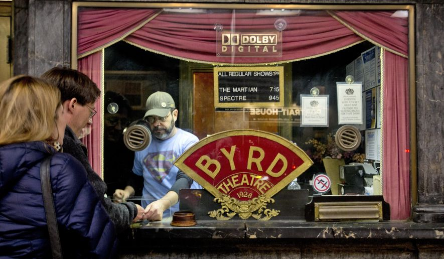 In this Jan. 20, 2016 photo, patrons purchase tickets at the box office of the Byrd Theater in Carytown a neighborhood a few miles west of downtown Richmond, Va. The Byrd Theatre is an 88-year-old movie palace that shows second-run movies for $2 a ticket. (AP Photo/Steve Helber)