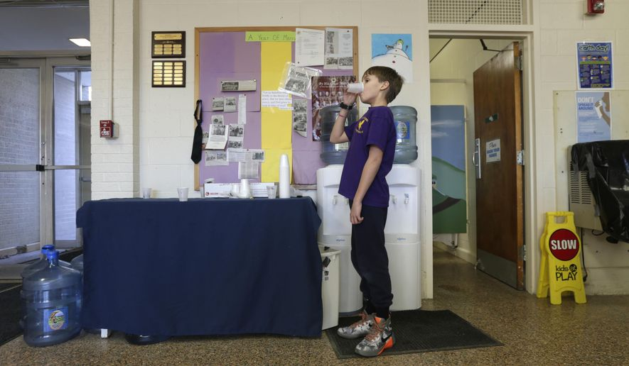 In this Thursday, Jan. 21, 2016 photo, Zander Spurr, a fifth grader at St. Mary's Academy, drinks water from a water bottle that has been set up in the school in Hoosick Falls, N.Y. Federal regulators have warned residents of the upstate New York factory village near the Vermont border not to drink water from municipal wells, and a plastics plant has agreed to supply bottled water and pay for a new filtration system. (AP Photo/Mike Groll)