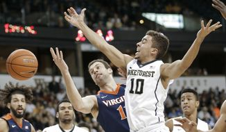 Wake Forest's Mitchell Wilbekin, right, is fouled by Virginia's Evan Nolte, left, in the first half of an NCAA college basketball game in Winston-Salem, N.C., Tuesday, Jan. 26, 2016. (AP Photo/Chuck Burton)