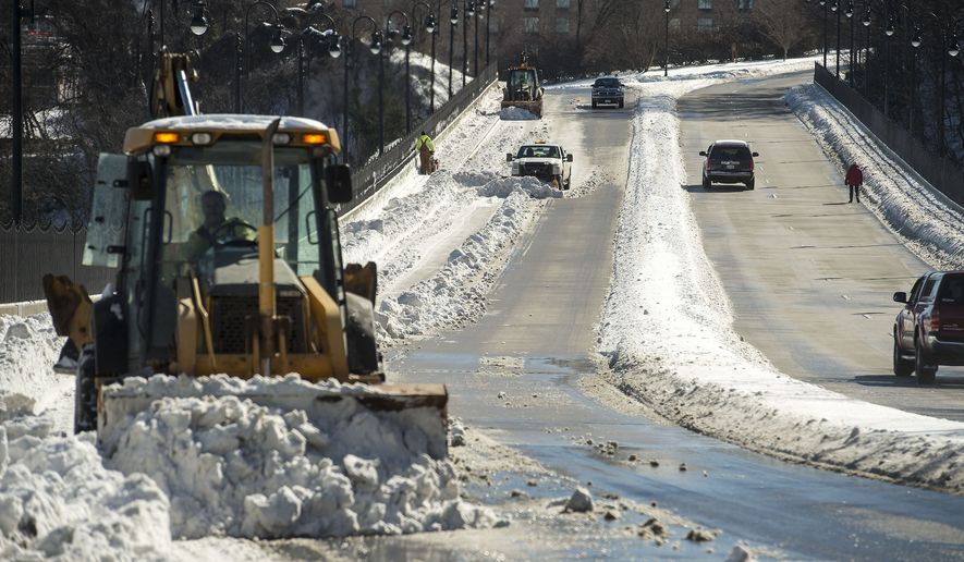 Crews clear the Rivermont Avenue Bridge of snow on Sunday, Jan. 24, 2016 in Lynchburg, Va. Despite the break in the weather, the Virginia Department of Transportation is echoing the advice of Gov. Terry McAuliffe: stay off the roads. (Jay Westcott/The News & Advance via AP)