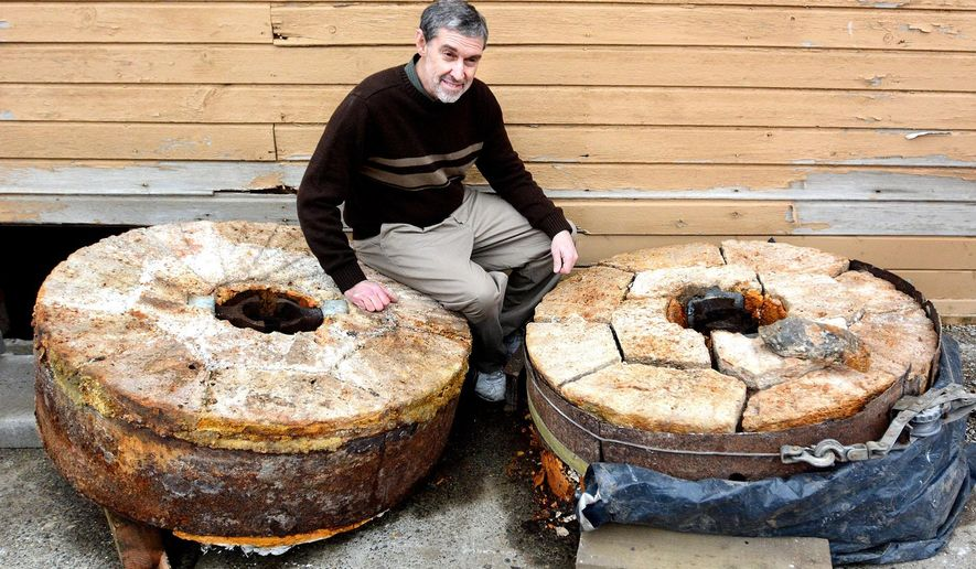 ADVANCE FOR USE SATURDAY, JAN. 30 - In this photo taken Jan 19, 2016, Pastor John Van Vogt poses by two giant, extremely heavy millstones unearthed from under the Pataha Flour Mill in Pataha, southeastern Washington. (Barry Kough/Lewiston Tribune via AP) MANDATORY CREDIT