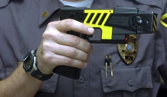 FILE - In this Oct. 28, 2004 file photo, an officer holds a stun gun used by his police department in a Farmington, Conn.  (AP Photo/Bob Child, File)