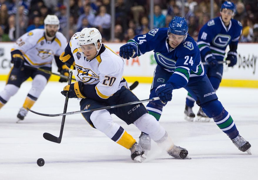 Nashville Predators' Miikka Salomaki (20), of Finland, moves the puck past Vancouver Canucks' Adam Cracknell (24) during first period NHL hockey action in Vancouver, British Columbia, Tuesday, Jan. 26, 2016. (Darryl Dyck/The Canadian Press via AP)