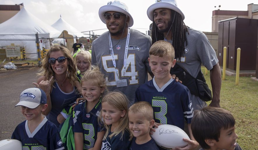 Seattle Seahawks middle linebacker Bobby Wagner (54) and cornerback Richard Sherman (25) pose for pictures with fans before the NFL football Pro Bowl draft Wednesday, Jan. 27, 2016, at Wheeler Army Air Field in Wahiawa, Hawaii. (AP Photo/Marco Garcia)