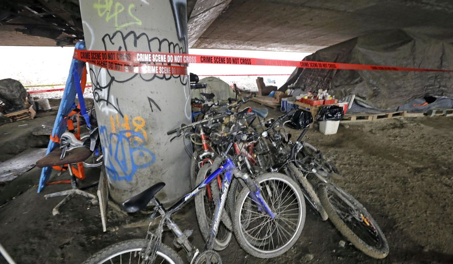 "Bicycles remain stacked against a support post for Interstate 5 above as crime scene tape surrounds the site of a shooting the night before at a homeless encampment, Wednesday, Jan. 27, 2016, in Seattle.  A homeless man and woman were killed and three other people were wounded when a shooting erupted at the homeless encampment known as 'The Jungle,' authorities said. The victims lived at the encampment where the attack occurred Tuesday evening and investigators ""have reason to believe it was very targeted,"" Assistant Seattle Police Chief Bob Merner said. (AP Photo/Elaine Thompson)"