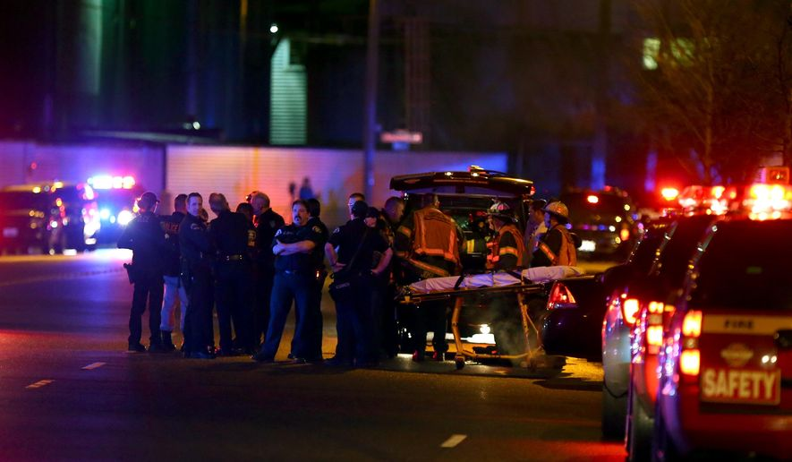 Law enforcement and medics respond to a shooting near Airport Way South and Atlantic Street on Tuesday, Jan. 26, 2015 in Seattle. Police say two people have been fatally shot and three others wounded by gunfire at a homeless encampment.  (Dean Rutz/The Seattle Times via AP)