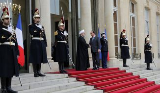 French president Francois Hollande, center  right,  welcomes Iranian President Hassan Rouhani before a meeting at the Elysee Palace, in Paris, Thursday, Jan. 28, 2016. France has welcomed Iranian President Hassan Rouhani with a lucrative car-making agreement and pledges to boost trade after a diplomatic deal easing nuclear tensions. (AP Photo/Christophe Ena)